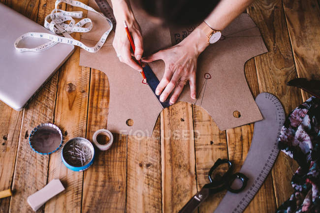 Fashion designer drawing around pattern — Stock Photo
