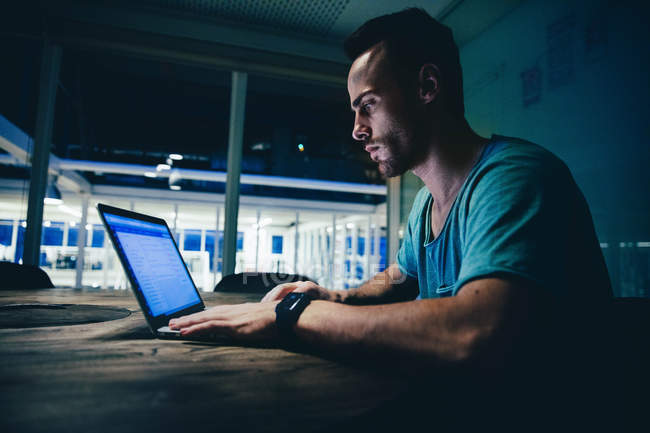 Man working on laptop in office at night — Stock Photo