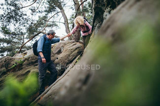 Пара походы по скалам в лесу — стоковое фото