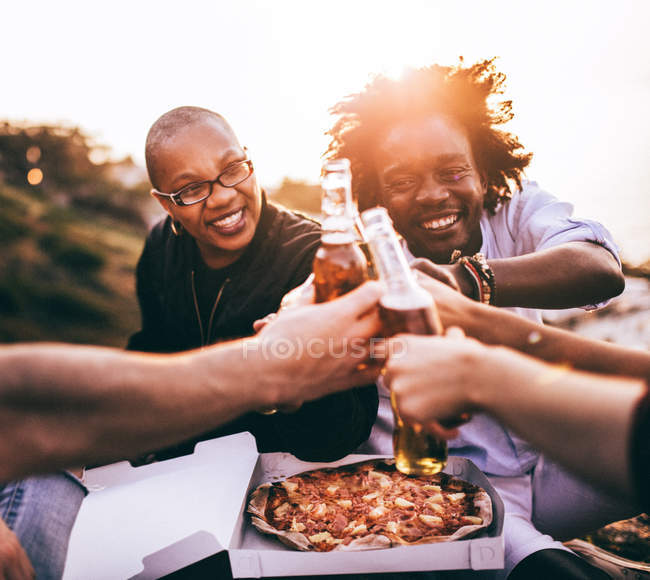 Friends enjoying drinks and pizza — Stock Photo