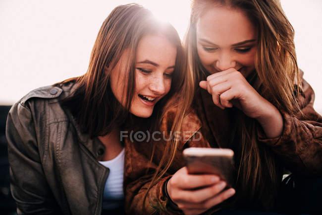 Girls using smartphone — Stock Photo