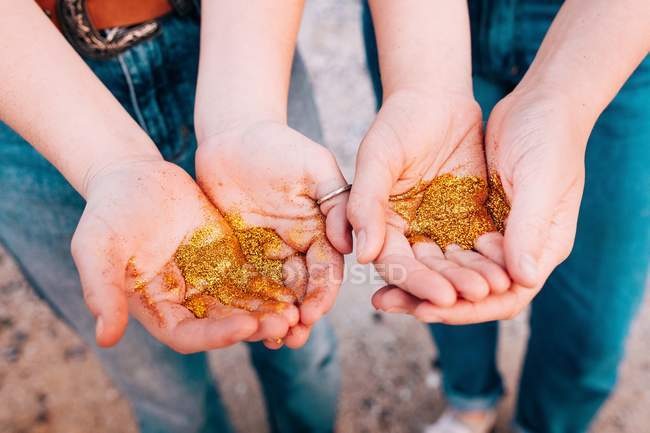 Female hands holding golden glitter — Stock Photo