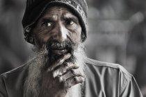 Uomo indiano che osserva via con la mano sul mento — Foto stock