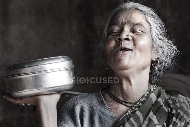 Indian woman laughing and holding metal bowl — Stock Photo