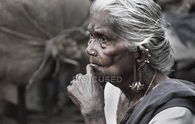 Indian woman with hand on chin looking away — Stock Photo