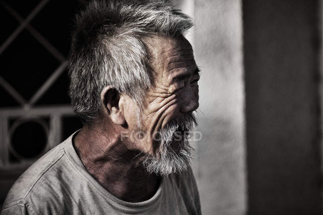 Thai man smiling and looking away — Stock Photo