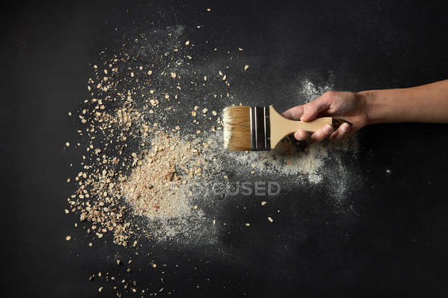 Hand with brush and breadcrumbs — Stock Photo