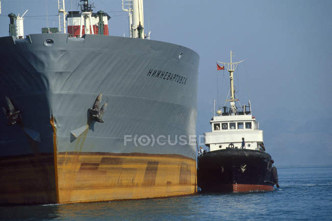 Tug towing cargo ship — Stock Photo