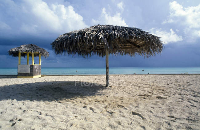 Тропический пляж и зонтик — стоковое фото