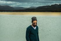 Man in pullover standing on seashore — Stock Photo