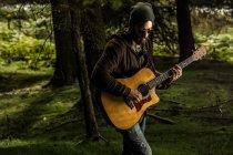 Mann spielt Aukustikgitarre auf Wiese — Stockfoto