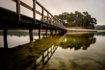 Wooden dock to lake island reflections — Stock Photo
