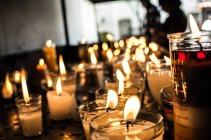 Rows of burning candles — Stock Photo