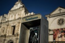 Street telephone with church in background — Stock Photo