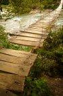 Ponte in legno sul fiume di montagna — Foto stock