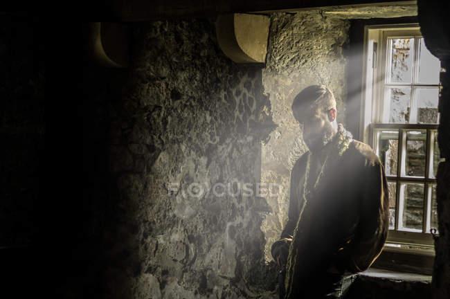 Чоловік стоїть біля вікна всередині будинку — стокове фото