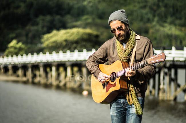 Bärtiger Mann spielt Akustikgitarre — Stockfoto