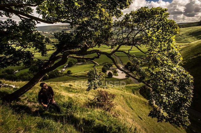 Людина, відпочиваючи під дерево під час прогулянки по нагір'я — стокове фото