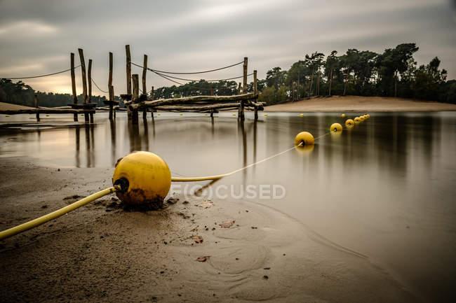 Жовтий буї на березі озера — стокове фото