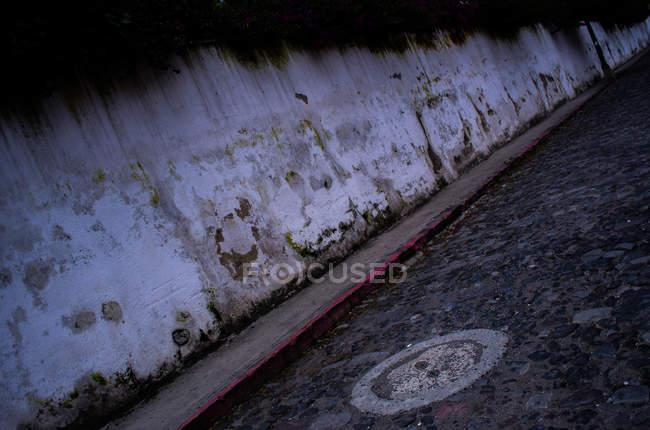 Ragged wall and urban pavement — Stock Photo