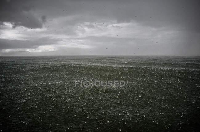 Heavy rain falling in sea — Stock Photo