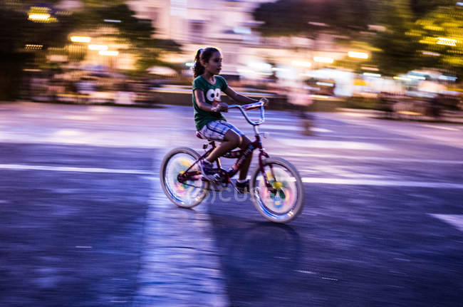 Girl riding bike on street — Stock Photo