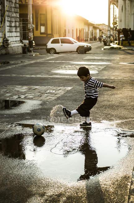 Menino jogando futebol na poça — Fotografia de Stock