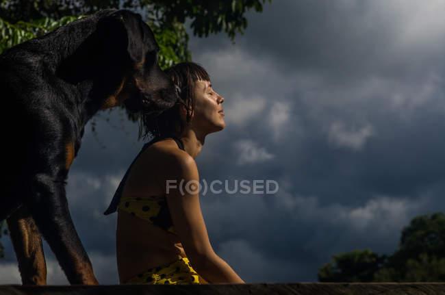 Mulher tomando banho de sol com cachorro — Fotografia de Stock