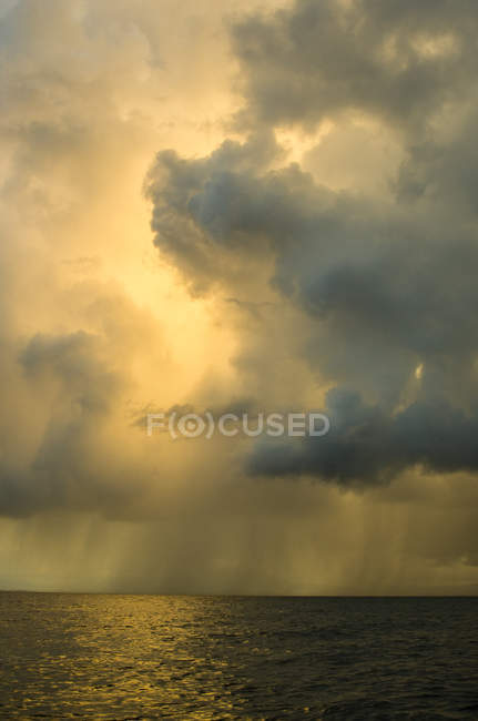 Showers from rain clouds over ocean — Stock Photo