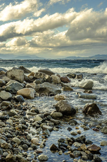 Waves crashing on stones at seashore — Stock Photo