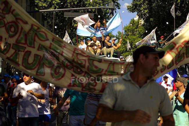 Людной улице с людьми, которые держат флаги — стоковое фото