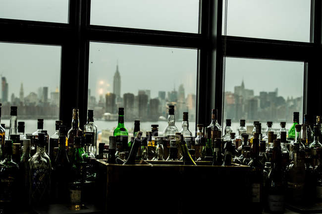 Row of bottles with New York cityscape — Stock Photo