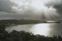 Stürmische Wolken und Sonnenstrahlen über Küstenort — Stockfoto
