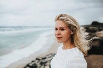 Woman standing on beach shore — Stock Photo