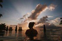 Mulher sentada na água e olhando a paisagem — Fotografia de Stock