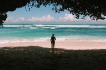 Frau, die von natürlichen Höhle nach Meer — Stockfoto