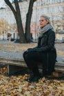 Жінка, сидячи на лавці в парку міста — стокове фото