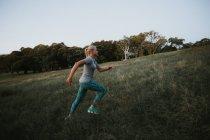 Спортивный женщина работает на холме в парке — стоковое фото