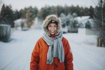 Женщина, стоящая в капюшоне и улыбающаяся в камеру — стоковое фото