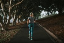 Sporty woman running in city park — Stock Photo