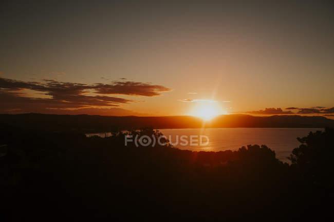 Montagne e superficie dell'acqua durante il tramonto — Foto stock