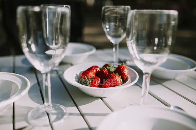 Ajuste de mesa con tazón con fresas en el centro - foto de stock