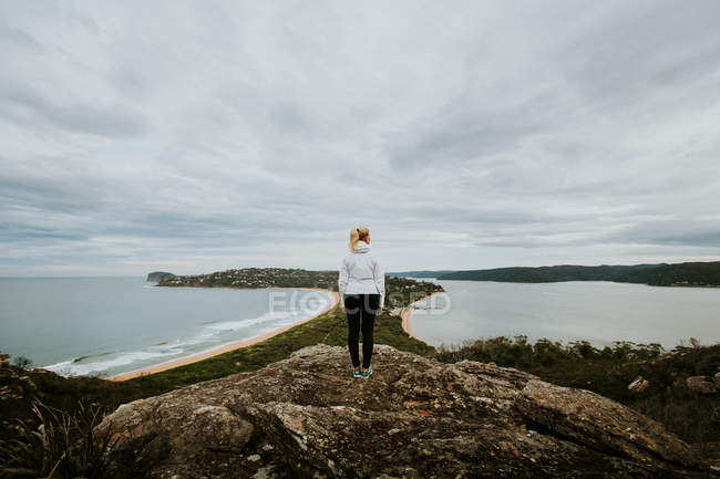 Woman standing on rock and looking at beautiful landscape — Stock Photo