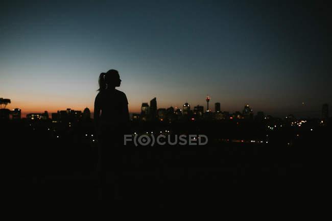 Femme s'étirant contre la ville à l'horizon — Photo de stock