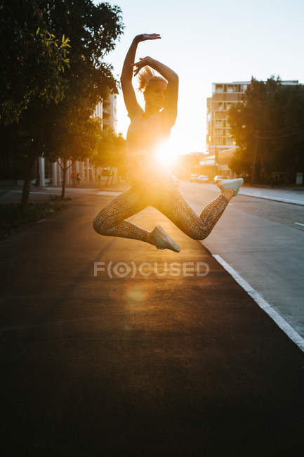 Woman jumping in ballet posture on street — Stock Photo