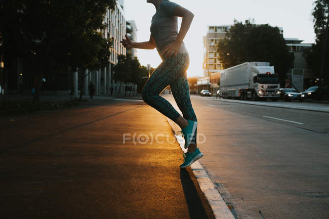 Woman starting running on urban street — Stock Photo