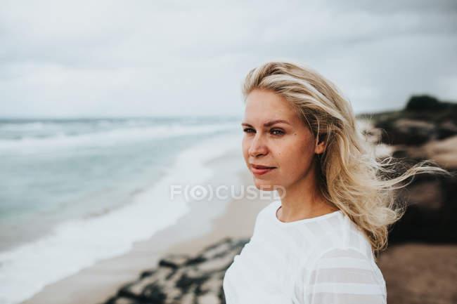 Жінку, що стоїть на березі пляжу — стокове фото