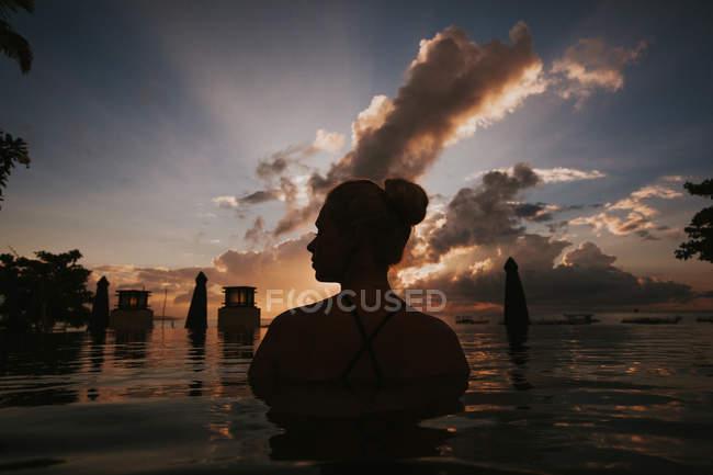 Жінка сидить у воді і, дивлячись на морський пейзаж — стокове фото