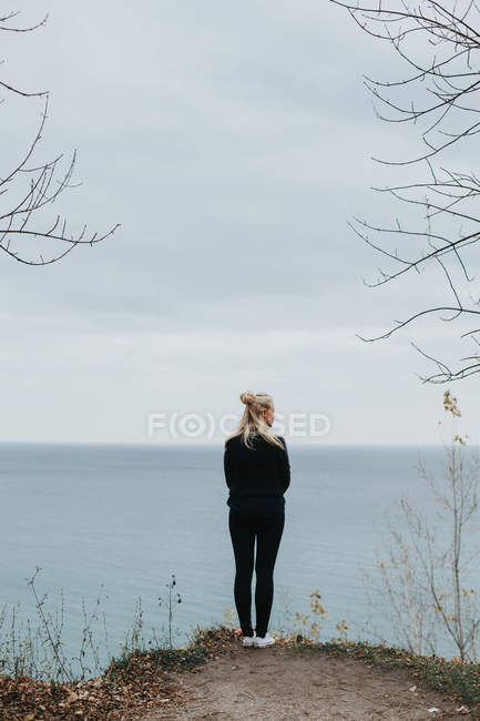 Woman standing on rock and looking at seascape — Stock Photo