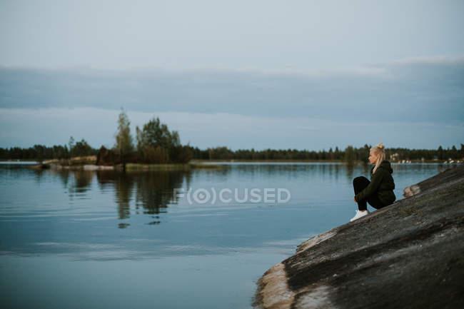 Donna che si siede sulla riva del fiume — Foto stock